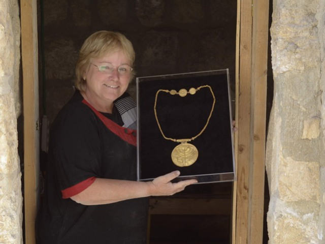Eilat Mazar holding a gold medallion etched with menorah, shofar and Torah scroll (Photo by Ouria Tadmor/Eilat Mazar)